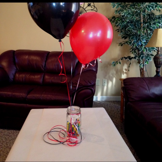 Crayons in a mason jar with balloons tied on covered