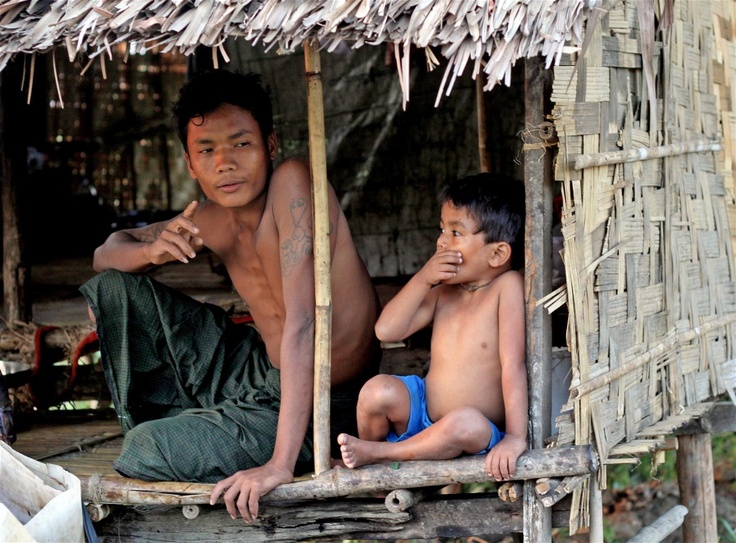 Father and son prepare to turn in for the night at a riverside hut in a fishing village outside Myanmar's commercial capital, Yangon