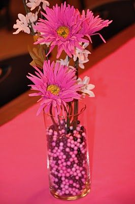 clear vase with black and white marble with some pink flower