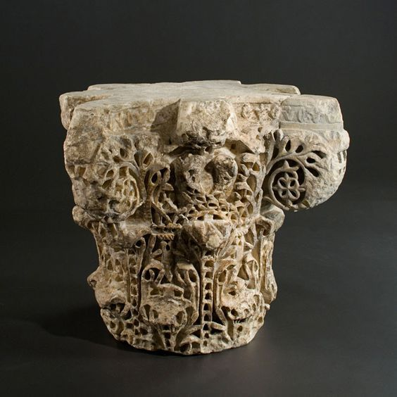 Islamic marble Umayyad capital, Caliphate period, 9th century A.D. The base is adorned with short chained stems that form with the foliage surmounting them, sort of a stylized tapering leaf. Long chained stems cover the first register and are surrounded by a characteristic crowned comma pattern. The second register is composed of a crossed lyre-shaped pattern. The volutes are formed by a foliate stem that frames a quadrilobed flower nestled within the spiral, 29 cm high. Private collection