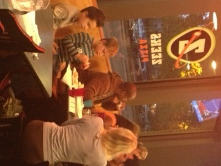 MomsRising members and kids at a Seattle pizza place, watching the debate and playing debate BINGO together!