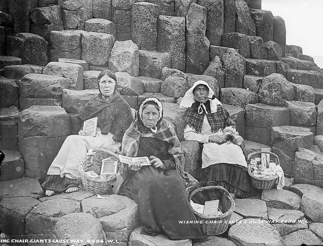Wishing Chair    Three women sitting on Fionn Mac Cumhaill's (Finn Mac Cool) Wishing Chair at the Giant's Causeway, Co. Antrim. They're selling tourist trinkets and books containing views of the locality. Note the woman on the left is barefoot.