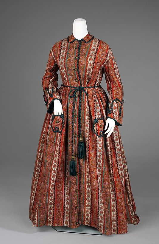 Red printed wool dressing gown with teal green silk cord trim and belt, American, ca. 1875. Seen here is a quintessential dressing gown of the period with military-style cuffs, cord belt and paisley pattern. This was a popular style in the mid- to late-Victorian period, for while the popularity of paisley shawls had waned, the pattern lived on in various other permutations. This dressing gown is a particularly nice example because the teal color is carried throughout in the pattern and the co...: History, Museums, Dressing Gowns Wrappers, Gown 1875, 1870S, Clothing, Historical Fashion, Art, Metropolitan Museum