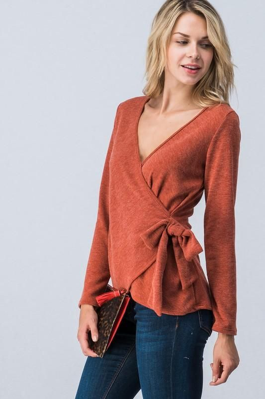 300553640 A solid hued, knit faux wrap style top featuring a v-neckline and a tie-closure  on the side. Top is stretchy enough to pull down/aside for nursing friendly  ...