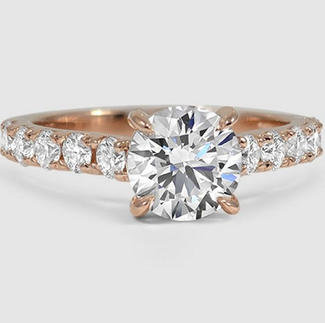 This luminous ring secures the center diamond with elegant claw prongs and features glamorous French pavé diamonds.