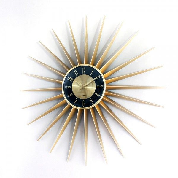 The Sunburst clock has twenty-four gold colored aluminum rays radiating out from a round central core. Matching gold colored minute and hour hands sweep out time over a black and gold dial face with g