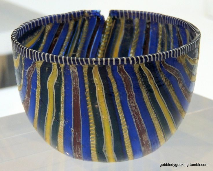 Striped Millefiori Cup. is a type of mosaic glassware characterized by a distinctive flower-like pattern. The technique was invented by the Egyptians and was known to be used by Alexandrian craftsmen to create beads. Glass. H. 6.6 cm, D. (max) 10 cm. Created during the reign of Augustus (27 BCE- 14 CE). National Archaeological Museum, Florence
