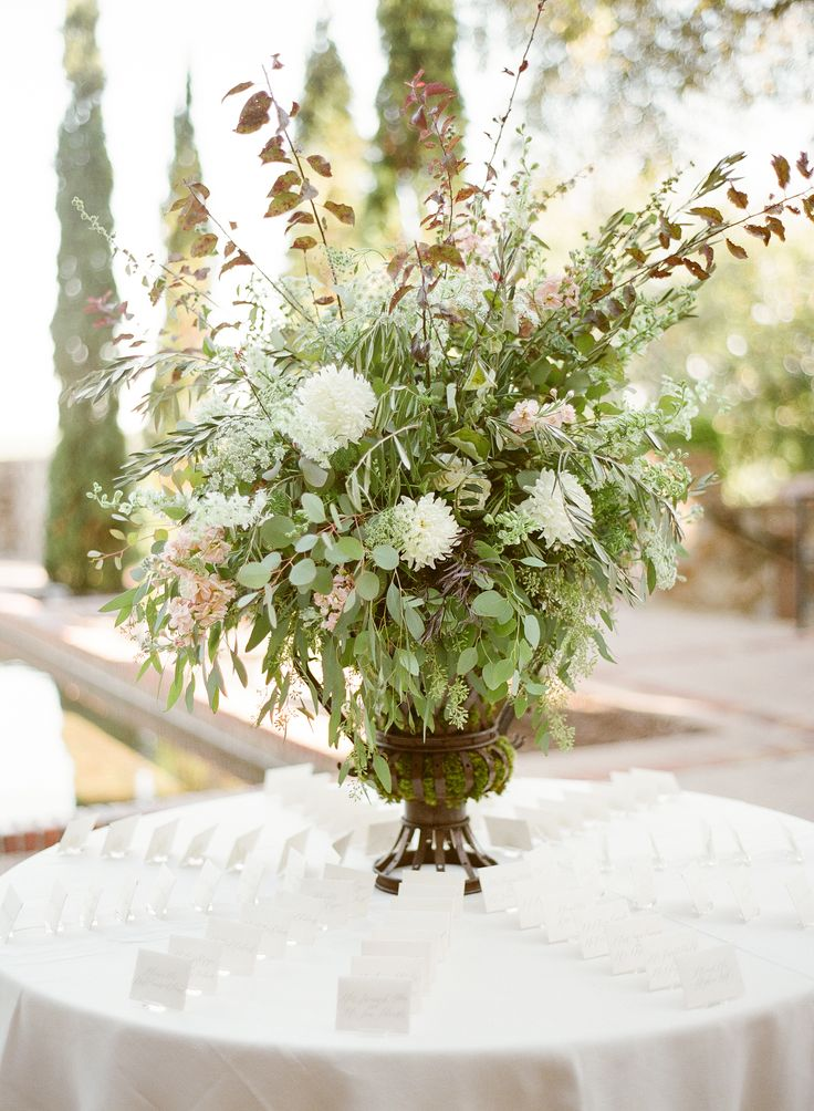 escort card display table is highlighted by a cascading arrangement of  purple plum branches, olive branches, eucalyptus, white majolik spray rose, peach stock, white larkspur, large cream mums, queen anne's lace, seeds and berries  in a large mossed garden urn.