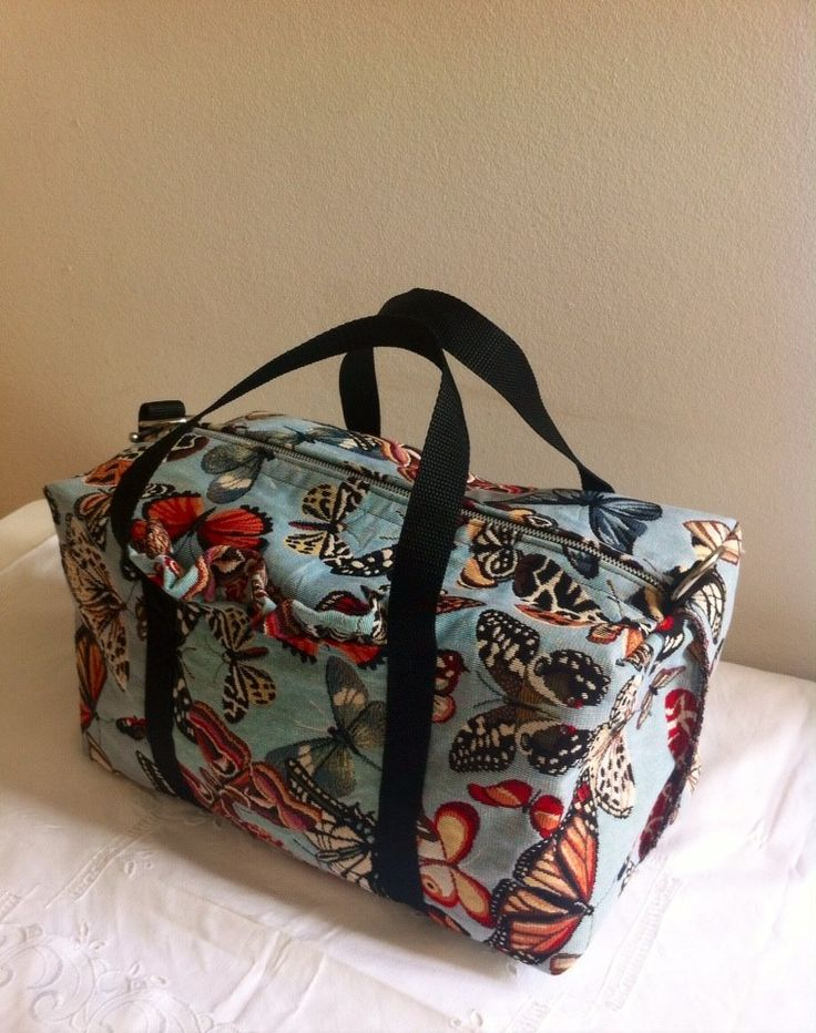 Sports bag in butterfly tapestry fabric, self-lined. Black straps, frilled pocket and cross-body detachable strap attached with silver d-rings.
