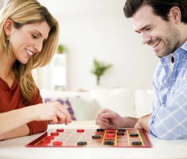 Couple playing checkers together - Jamie Grill/The Image Bank/Getty Images