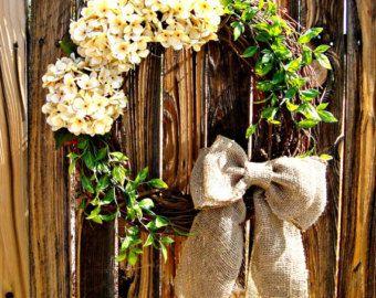 La corona de Katelyn hará una fantástica adición a su puerta! Cuenta con 3 hermosas hortensias color turquesa y eucalipto verde pálido atado a una corona de vid y atado con un lazo de arpillera color turquesa. En la foto con un monograma blanco, elige el color y el monograma inicial como para que sea personal. Mide aproximadamente 20 de diámetro.  Cada flor, el arco y la letra es pegado y atado con alambre a la corona para la durabilidad óptima