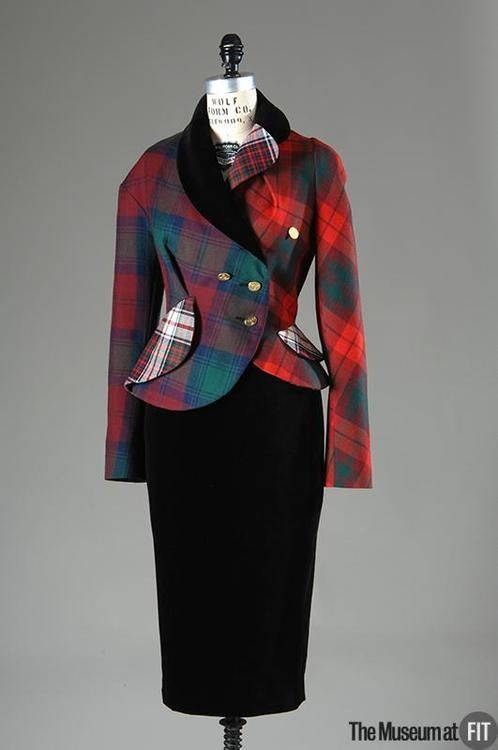 Vivienne Westwood ~ wool tartan, black silk and velvet suit. 1993.  This suit incorporates elements of Vivienne Westwood's fascination with traditional British dress, specifically in its precise tailoring and use of tartan fabric. She irreverently combines these elements with asymmetrical design and mixes tartans to create a suit that reflects her creativity and eclecticism.