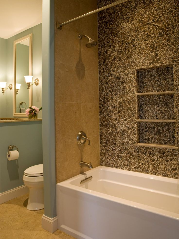 pebble tiles decoratively accent the bathtub wall and blend with the green and neutral tones in this transitional bathroom