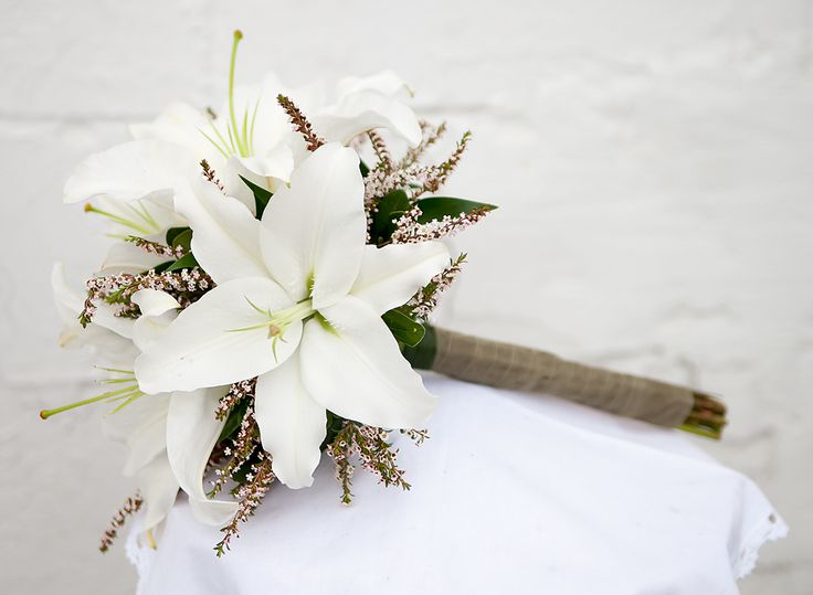 White Lillie's with yellow ragweed instead of accent shown. Navy ribbon hand tied stem.