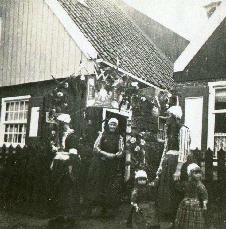 De steeg waar Bessie van Mekurft woont is op Koninginnedag versierd met papieren rozen en guirlandes. Van links naar rechts staan Peet Aaltje en Bessie. op Marken