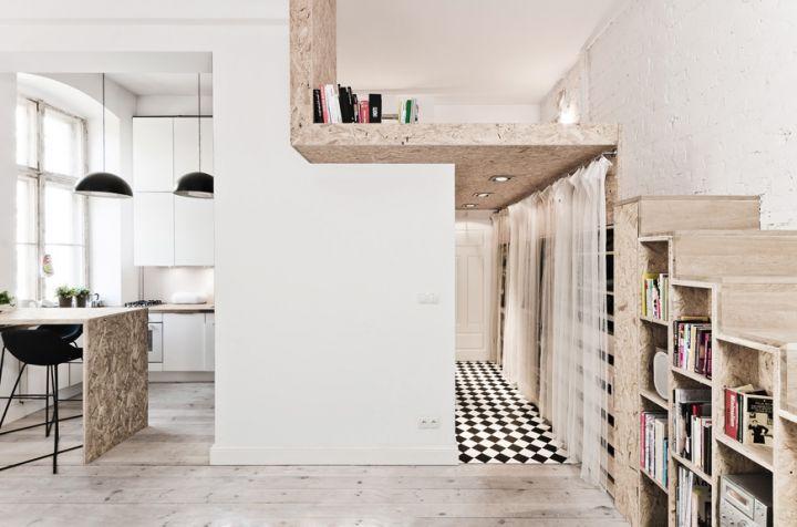 In foto un primo piano del loft/camera da letto alla quale si accede grazie ad una scala in legno che funge anche da libreria e contenitore. Sotto al soppalco è visibile la porta d'ingresso e il mini corridoio
