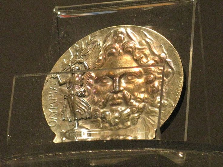 Silver (first place) medal with the face of Zeus, his hand holding a globe surmounted by winged Victory.