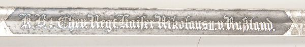 DETAIL OF AN IMPERIAL GERMAN BAVARIAN M89 CAVALRY SWORD WITH ENGRAVED BLADE, ca. 1910. Straight fullered blade, blade length 29.25 inches, with engraved unit designation 'K.B. 1. Chev. Regt. Kaiser Nikolaus II. v. Russland.'. Hilt has nickel guard with rampant lion motif, Bakelite grip and sword knot. Complete with black painted steel scabbard. The Russian Czar, Nicholas II was the honorary commander of the 1st Bavarian Chevaulegers Regiment from 1894 to 1918. Jackson's International…