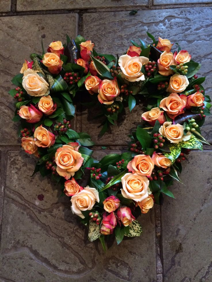 Rose heart- I like the dark glassy leaves and the warm peach roses and the use of the hypericum berries
