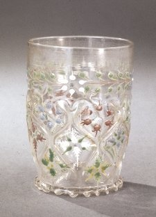 Beaker; glass; denticulated base-ring and kick; lozenge-shaped, partially gilt, raised ribbing on lower half of beaker; pattern contains stylised floral patterns enamelled in greens, red, blue and white; floral and foliate band at top. 1450-1500