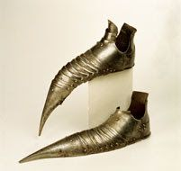 Sapatos de armadura em ferro, de bico revirado. Ano de 1490 - MMA No século XVI os sapatos deixaram de ser pontiagudos, passaram a apresentar bicos largos chamados bicos de pato. A sola é de couro ou cortiça, a parte superior de couro,  por vezes de veludo ou seda, adornados com recortes e jóias.
