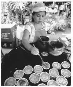A Mexican woman prepares tortillas with salsa and beans. Corn, chili peppers, and beans are the main items in most Mexican foods.