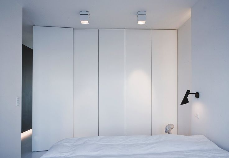 AJ wall lamp by Arne Jacobsen | Louis Poulsen | Bedroom with full height closets.