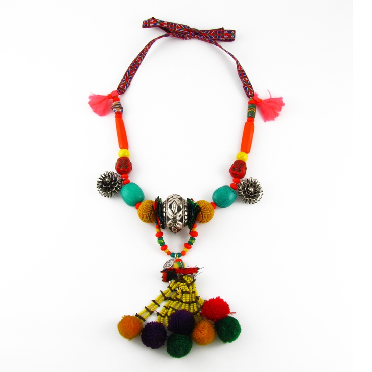 Ribbon tapes and metal flowers found in remote China made by the Miao tribe, African trader beads and fabric, an Afghani pom pom tassel, Asian resin, the centre metal bead is from India.