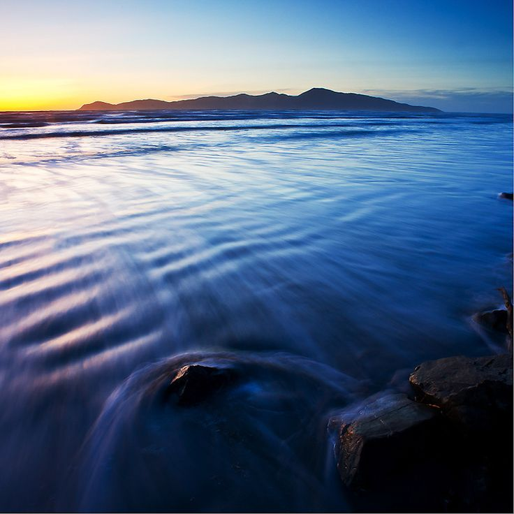Waves sweep over a rock on Raumati South Beach just as the sun goes down. Raumati South, near the northern entrance to Queen Elizabeth Park, Kapiti Coast, North Island, New Zealand. Ref: NZNK169037