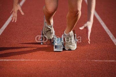 female sprinter leaving the starting blocks on a track