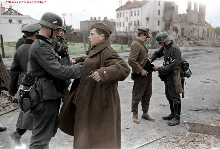 Captured Polish soldiers being searched by German soldiers during the invasion of Poland