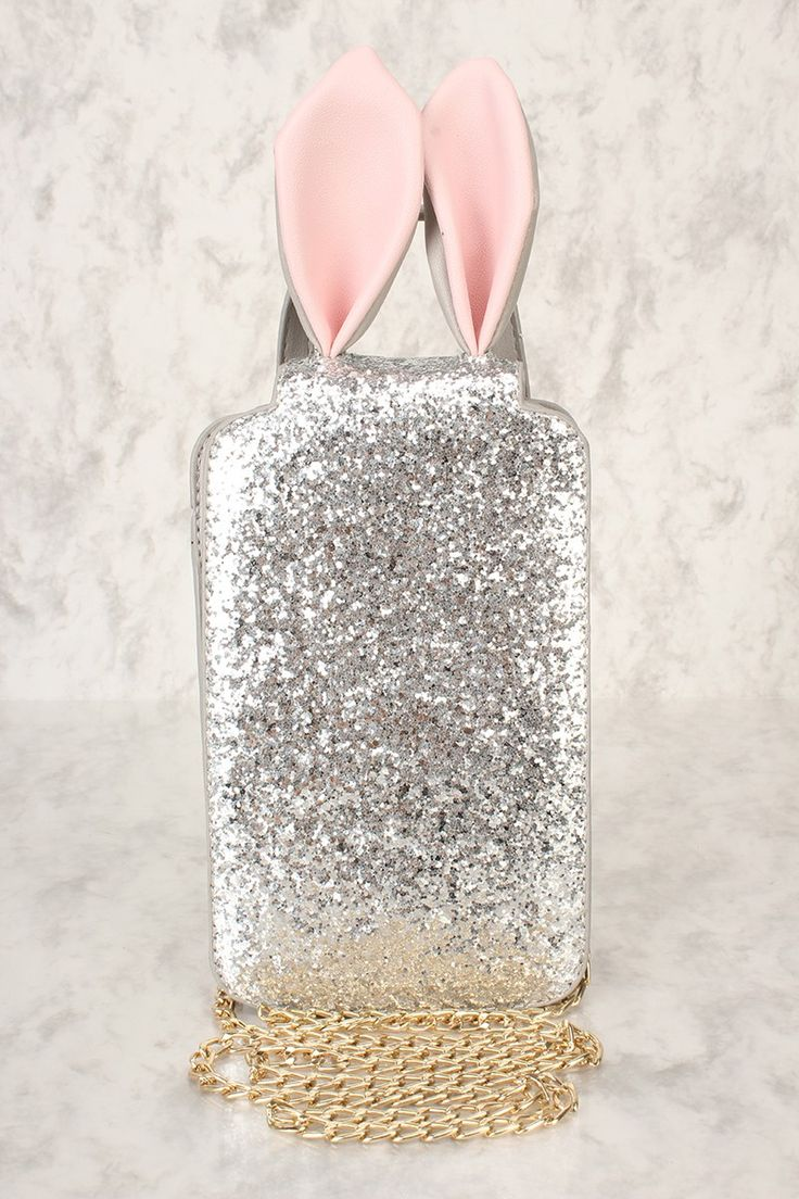 Take this bold handbag with you wherever you go for an eye catching look! Featuring; faux leather, glitter, bunny ears, back handle, high polish metal detailing, stitch trim, clasp closure, removable chain shoulder strap. Width: 4 3/4 inches Height: 11 1/2 inches Depth: 3inches