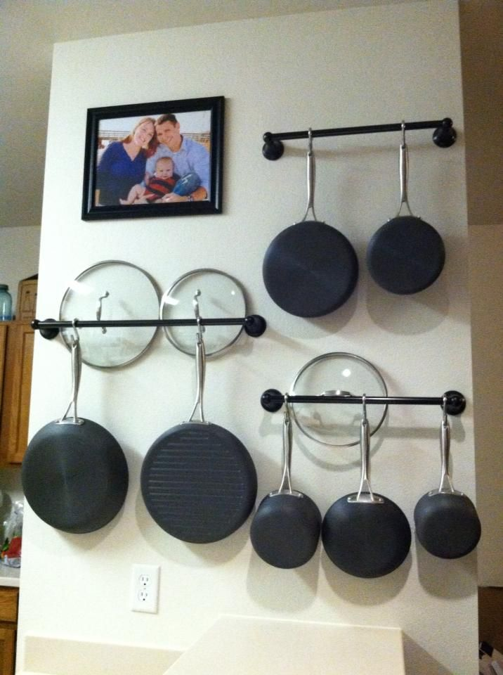 Hang pots and pans on towel racks to create more cabinet space! ~~~ Dang this is better than my current method. May have to switch! My lids are taking up a whole shelf