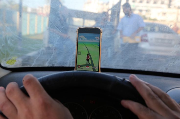 A Palestinian woman rests her smartphone on a car dashboard as she plays Pokemon Go in Gaza city