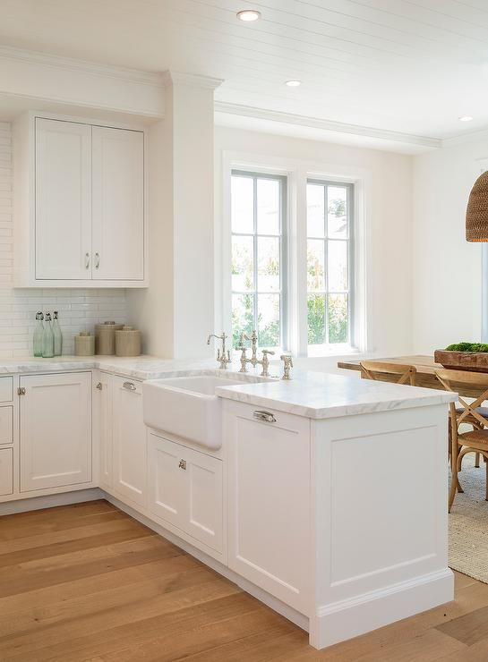 A stunning white kitchen peninsula boasts a farmhouse sink with a polished nickel vintage deck mount faucet fixed to a marble countertop positioned atop white shaker cabinets adorning polished nickel hardware.