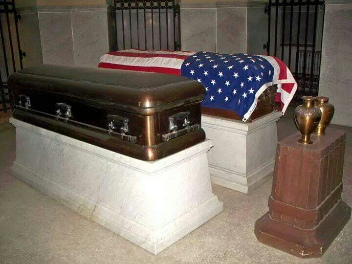 President Garfield and his wife are entombed in the Garfield Memorial in Ohio. This photo shows the caskets of  President James A. Garfield (covered with a US flag) and his wife, Lucretia Rudolph Garfield (1832-1918), both on biers. In the urns at the head of the caskets are one of their daughters, Mary Mollie Garfield Stanley-Brown (1867-1947) and her husband Joseph Stanley-Brown (1858-1948).