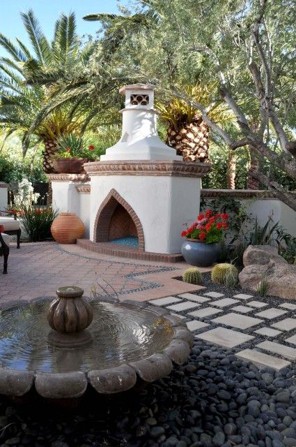 A mediterranean style terrace is embellished with a water for Mediterranean fireplace designs