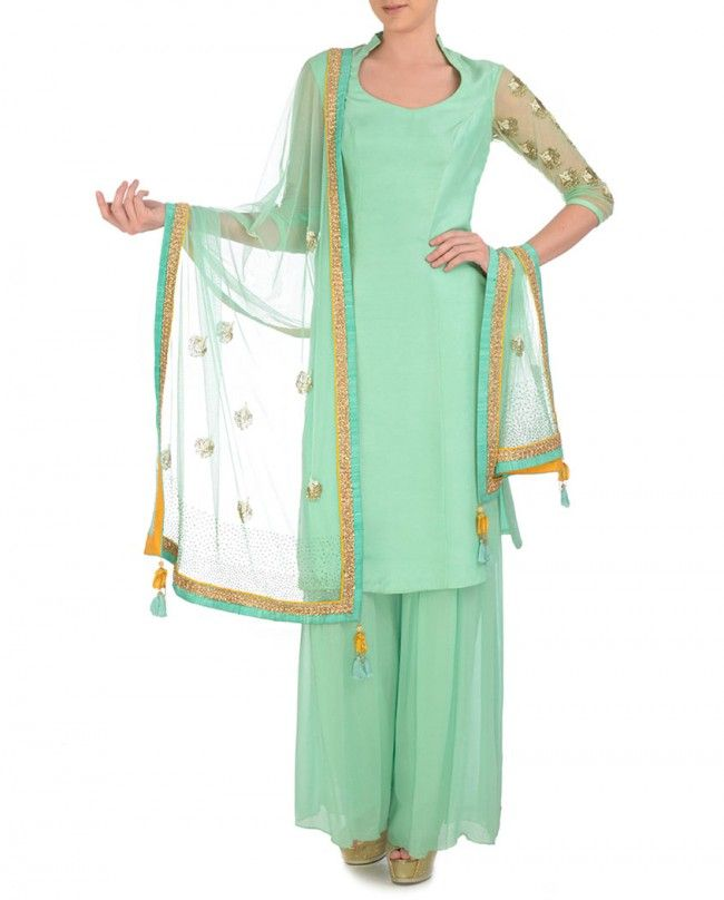 Mint green kurta with sheer detailing at back. Golden bugle bead and embellished patterns accentuate the sheer back. Chinese collar with scoop neck. Three quarter sleeves with sheer detailing and bugle bead embellishments. The set also includes matching sharara pants and embellished dupatta.  Wash care: Dry clean only visit -www.suitsaristore.com www.facebook.com/designersuitsandsari