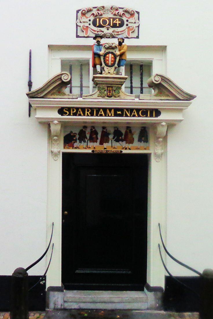 Het witgepleisterde pand aan de andere kant van de straat is het Oude Mannenhuis of Willem Vroesenhuis. De gevelsteen met houtsnij- en beeldhouwwerk vermeldt 1614 als bouwjaar van de poort. Boven de poort – nu met deur – houden twee oude mannen het wapen van Gouda vast en het verstrijken van de tijd wordt gesymboliseerd door een zandloper. De afbeelding daaronder vertoont drie regenten en enkele behoeftige oude mannen. De spreuk luidt 'Spartam nacti'.