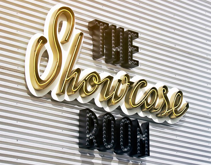 """An open face channel letter with exposed neon is used to create """"Showcase."""" Exposed LED filament bulbs recessed into channel letters spell out """"The Room."""""""