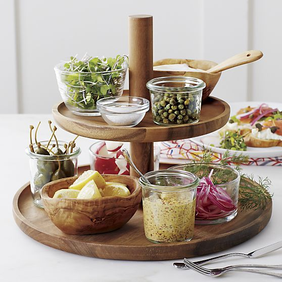 Use separately or stacked as a pedestal, these contemporary coupe-shaped platters showcase sweets and savories with the rich grain of natural acacia wood. Raised rims keep foods on board; peg handles provide easy transport and secure the two sizes when stacked.