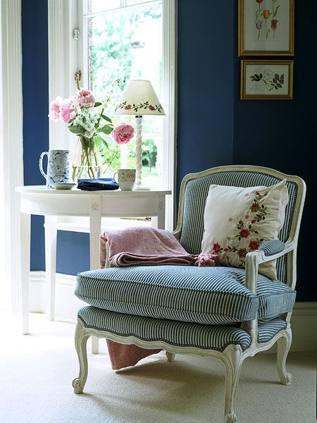 The dark saturated hue of indigo-painted walls works well in this light-filled room. An antique, French-style armchair covered in blue-and-white striped upholstery; a white demilune table; and delicate touches of pink balance the bright wall color. (Photo: IPC Images)