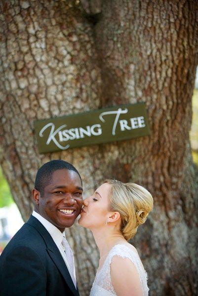 Fun garden wedding photo - love the idea of the kissing tree - The Tres Chic