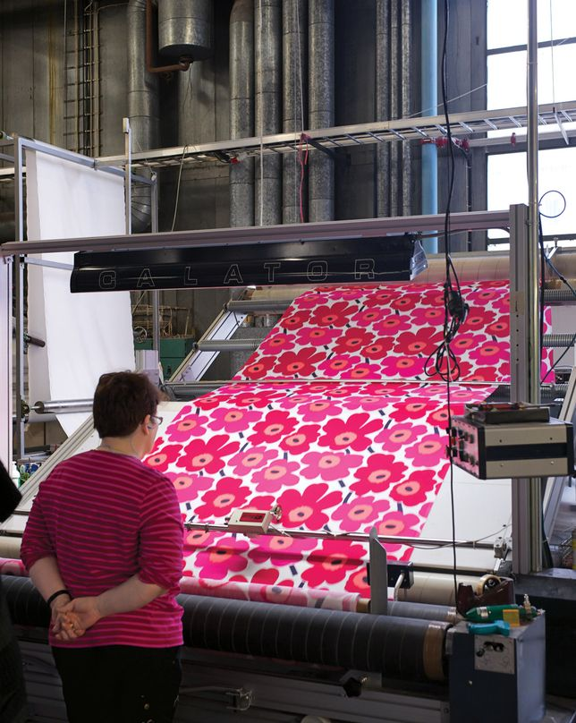 An inspector checks Pieni Unikko fabric.  #Marimekko #ClassicMarimekkoFabric #PieniUnikko