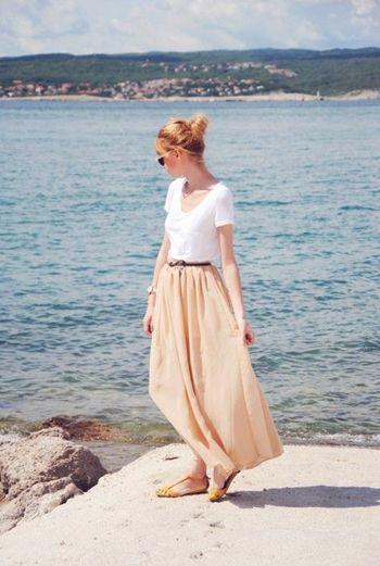 シンプルな白Tシャツにやさしいカラーのマキシスカートを合わせて。フラットサンダルを合わせてリラックスしたリゾート感のあるスタイリングです。