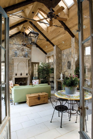 indoor/outdoor space includes a cathedral ceiling, limestone fireplace and a NanaWall system that opens to a  pool.