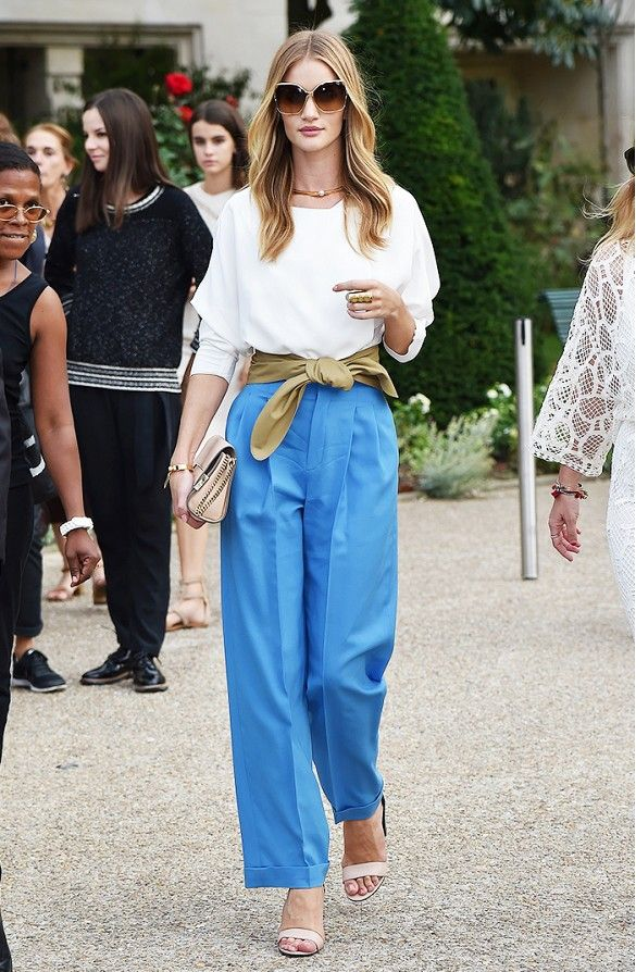 Rosie Huntington-Whiteley wears a white Chloé blouse, belt, and blouse wide-leg pants with neutral accessories