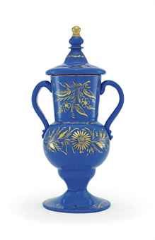 A BEYKOZ BLUE GLASS COVERED VASE  OTTOMAN TURKEY, 19TH CENTURY  With wide trumpet foot rising to rounded body with cylindircal slightly flaring neck, attached S-shaped handles to each side, with dome-shaped lid with double-knop finial, the surfaces with gilt floral decoration, rim and finial also gilt, intact  12¾in. (32.4cm.) high