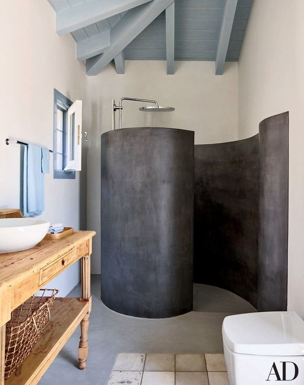 In a Greek home designed by Isabel López-Quesada, the poolhouse's coiling shower enclosure is fashioned of tadelakt, a waterproof Moroccan plaster; the showerhead is by Grohe | archdigest.com