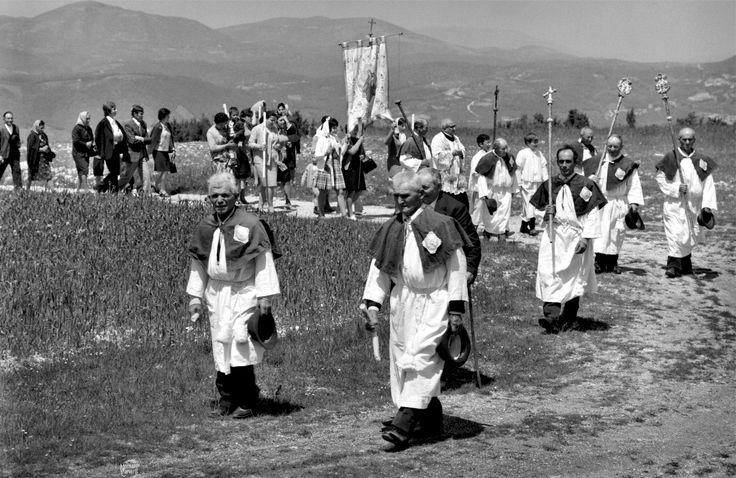 Postignano, Sellano, anni 60. La processione in onore di Santa Maria Assunta. Si snoda per le vie delle campagne del paese. Un lieve venticello solleva i lembi dello stendardo portato dalle donne del paese.